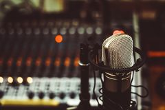 Microphone and mixing console. Professional condenser studio microphone over the musician blurred background and audio mixer, Musical instrument Concept Royalty Free Stock Photography