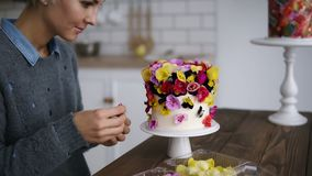 Professional confectioner woman decorates cake with flowers on white modern kitchen studio. Shorthair female chef makes. A wedding or birthday cake with fresh stock video footage