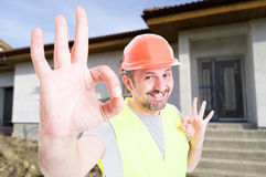 Professional construction services concept with cheerful builder. Showing ok sign with both hands stock photography