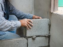 Professional construction worker laying bricks with cement stock photos
