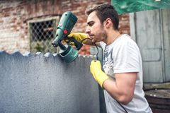 Professional construction worker painting walls at house renovation. Exterior building renovation with spray gun painter Royalty Free Stock Image