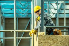 Professional Construction Worker. And the Skeleton Steel Frame of the Developed Building. Caucasian Worker in His 30s royalty free stock photos