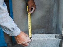Professional construction worker uses measuring Tape for measure and laying bricks with cement royalty free stock image