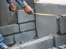 Professional construction worker uses measuring Tape for measure and laying bricks with cement.  royalty free stock photo