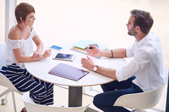 Professional consultant giving business advise to aspirational businesswoman. Young aspirational female entrepreneur getting professional business advise from a Stock Photos