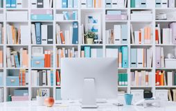 Professional contemporary workspace. Professional creative contemporary workspace with computer on a desk and colorful folders on the background Royalty Free Stock Image