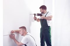 Professional contractor drilling in a white wall with a tool and. A handyman taking measurements with a tape royalty free stock photos