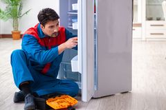 The professional contractor repairing broken fridge. Professional contractor repairing broken fridge Royalty Free Stock Photos