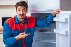 The professional contractor repairing broken fridge. Professional contractor repairing broken fridge Stock Photography