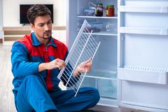 The professional contractor repairing broken fridge. Professional contractor repairing broken fridge Stock Photo