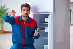 The professional contractor repairing broken fridge. Professional contractor repairing broken fridge Royalty Free Stock Photography
