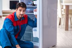 The professional contractor repairing broken fridge. Professional contractor repairing broken fridge Royalty Free Stock Image