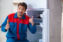 The professional contractor repairing broken fridge. Professional contractor repairing broken fridge Royalty Free Stock Photo