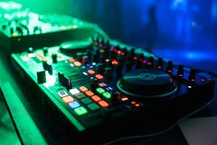 Professional control panel and mixing music under the green lights in nightclub at party Stock Photos