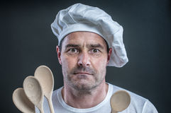 Professional cook. Cook with cooking spoon before black background Royalty Free Stock Photos