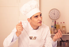 Professional cook is evulating prepared soup. On kitchen Stock Image