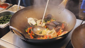 Professional cook is frying mussels and shrimps with vegetables at the street food festival. Roasted prawns and mollusk. Close up view. Process of cooking stock video