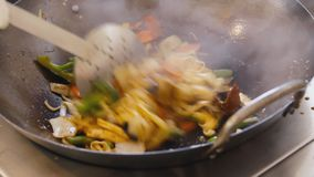 Professional cook frying vegetables with tofu and noodles at the street food festival. Process of cooking close up. Professional cook is mixing noodles and stock footage
