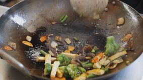 Professional cook frying vegetables with tofu at the street food festival. Process of cooking close up. Professional cook is mixing vegetables and tofu in a pan stock footage