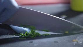 A professional cook in the kitchen cuts a bunch of parsley with a large knife. Proper nutrition and wellness. Prepare. And chop lush greenery for vegan. Eating stock video footage