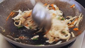 Professional cook is mixing noodles, vegetables and mushrooms in a pan at the street food festival. Process of cooking close up stock video footage