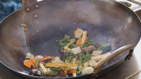 Professional cook frying vegetables with tofu and noodles at the street food festival. Process of cooking close up. Professional cook is mixing noodles and stock video footage