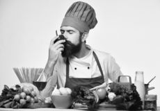 Professional cookery concept. Chef prepares meal. Cook with dreamy face. In burgundy uniform sits by kitchen table with vegetables and kitchenware. Man with stock photos