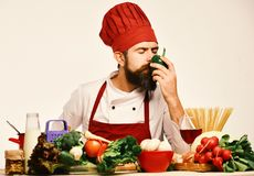 Professional cookery concept. Chef prepares meal. Cook with dreamy face. In burgundy uniform sits by kitchen table with vegetables and kitchenware. Man with stock photo