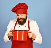 Professional cookery concept. Chef with red casserole or saucepan. Cook with excited face in burgundy hat and apron holds soup pot. Man with beard holds royalty free stock photo