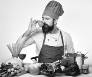 Professional cookery concept. Cook with dreamy face. In burgundy uniform sits by kitchen table with vegetables and kitchenware. Chef prepares meal. Man with royalty free stock photos