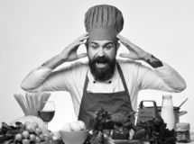 Professional cookery concept. Cook with shocked face in burgundy uniform. Sits by table with vegetables and kitchenware. Chef prepares meal. Man with beard royalty free stock photos
