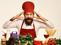 Professional cookery concept. Cook with shocked face in burgundy uniform. Sits by table with vegetables and kitchenware. Chef prepares meal. Man with beard royalty free stock images