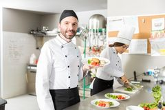Professional Cooks Working In Kitchen. Confident mid adult chef holding plate of chicken and vegetables in kitchen royalty free stock images