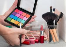 Professional cosmetic brushes, shadows, lipsticks and sponges on a gray table stock photos