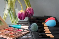Professional cosmetic brushes, shadows and sponges lie on a wooden table stock photos
