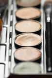 Professional cosmetic. Cream concealer palette in metal case. Expensive makeup brushes made of special fibers to work with creamy textures Royalty Free Stock Image