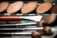 Professional cosmetic. Cream concealer palette in metal case. Expensive makeup brushes made of special fibers to work with creamy textures. Working with skin Royalty Free Stock Images