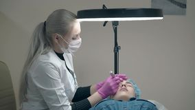 Professional cosmetician holds tattoo gun and lady forehead. Applying permanent make-up in beauty parlor stock footage