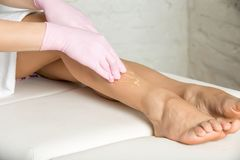 Professional cosmetician undergoing waxing procedure. Day of rest. Beautician waxing female legs in spa center Royalty Free Stock Image