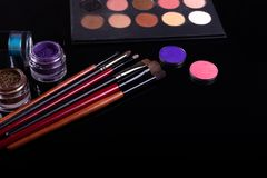 Professional cosmetics and brushes for make-up on a black background.  royalty free stock photo