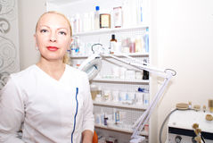 Professional cosmetologist. A woman working with cosmetics, stands in the middle compartment filled with equipment and creams and the means to care for body and Royalty Free Stock Image