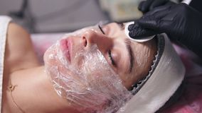 Professional cosmetologist is cleaning woman`s face from special treatment using cotton sponge. Young woman is lying on stock video footage