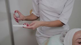 A professional cosmetologist disinfects the instrument with a special solution. Cosmetological innovations.  stock video