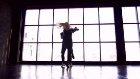 Professional couple of dancers studio. Brazilian zouk. A pair of dancers beautifully dance against the background of a. Large window closee-up slow motion stock video footage