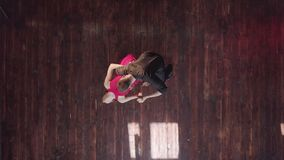 Professional couple dancing tango on the wooden floor in the studio.