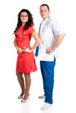 Professional couple of doctors. Beautiful nurse dressed in tangerine tango uniform and handsome doctor dressed in blue and white scrubs. Full body image isolated Royalty Free Stock Photos