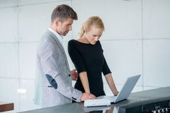 Professional Couple Looking Down at Laptop Royalty Free Stock Photos