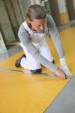 Professional craftsman installing plastic on floor surface Stock Image