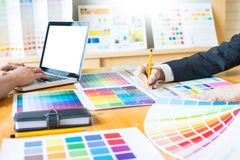 Professional Creative architect graphic desiner occupation choosing the Color pantone palette samples for project on office desk. Top computer stock photo