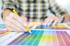 Professional Creative architect graphic desiner occupation choosing the Color pantone palette samples for project on office desk. Top computer royalty free stock photo